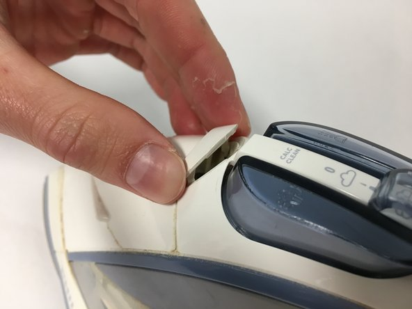 Image 1: Remove the plastic cover to expose the screw