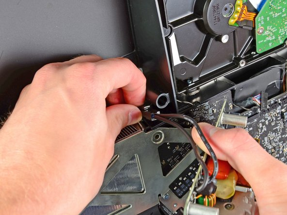Disconnect the AC-In cable by depressing the locking mechanism while pulling the connector away from its socket.