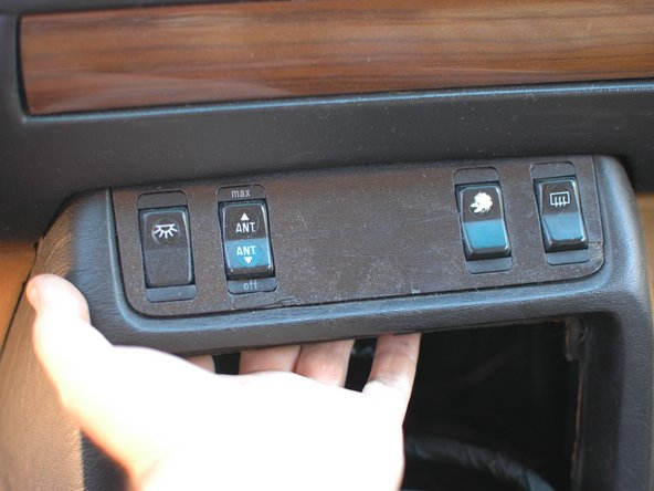 You can now reach up behind the wood trim in the center stack. Before removing the wood you must remove all of the switches. Push each switch out of the hole in the trim.