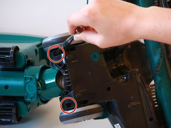 Using a T20 screwdriver, remove two 15.9 mm screws behind the vacuum wheels.