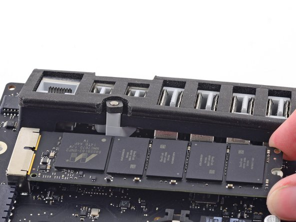Slightly lift the rightmost side of the SSD and firmly slide it straight out of its socket on the logic board.