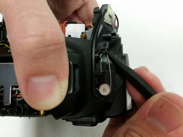Lift the flash arm spring using the plastic spudger and unhinge the spring to remove it.
