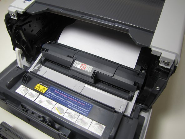 If jammed, paper will be visible after removing the drum unit. To clear paper jam, reach into printer and grab a corner of the paper.