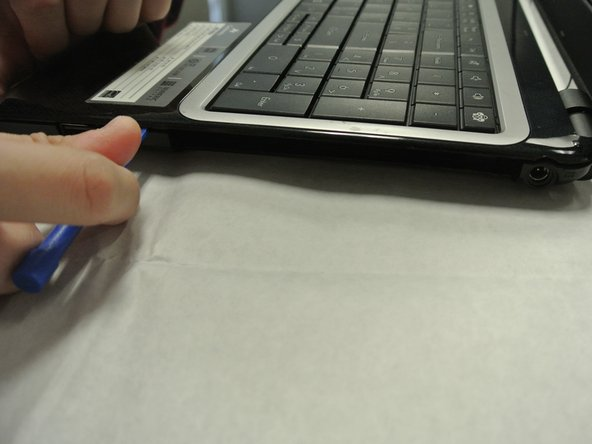 Use a plastic opening tool to pry open the sides of the laptop base starting closest to the hinges.