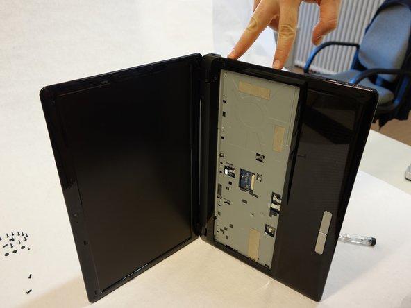 Um den Rahmen der Tastatur zu entfernen, beginne mit dem oberen Teil rechts.  (Visueller Zugriff zu den Clips durch die Öffnung des CD/DVD Laufwerkes), in dem du einen kleinen normalen Schraubenzieher oder besser ein kleines Gitarrenplättchen hineinschiebst.
