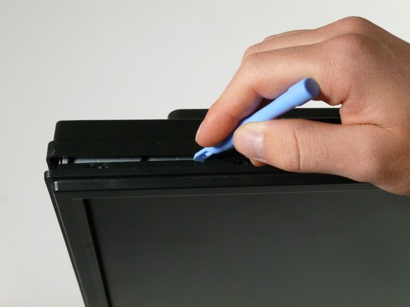 Starting at the corner of the monitor, wedge the small plastic opening tool between the back cover and the display bezel.
