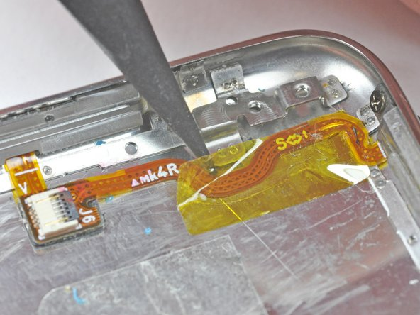 Use the tip of a spudger to remove the yellow kapton tape covering the power/volume control ribbon cable.