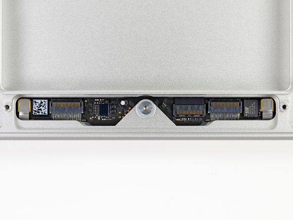 The trackpad board contains several connectors and two prominent ICs: