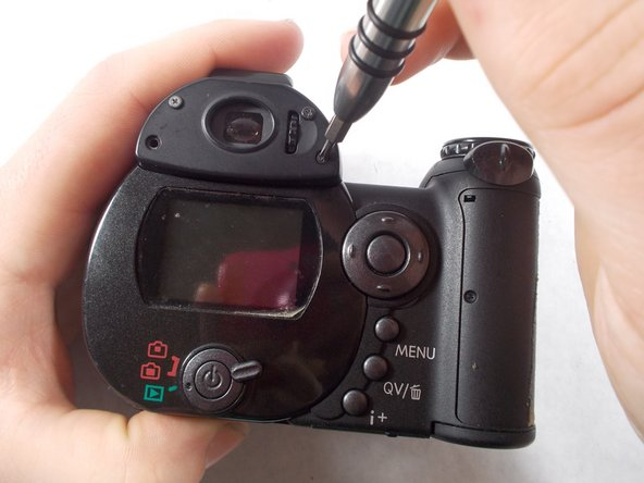 Use a screwdriver to remove the four viewfinder cover screws.