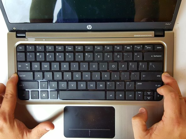 Slide the keyboard up and towards the screen just enough to separate the keyboard from the top cover.