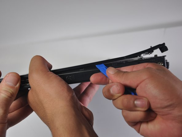 Using the iFixit opening tool, pry the black plastic panel (with mousepad) off of the motherboard.