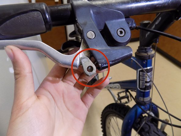 Apply pressure to the brake to reveal the end of the brake cable.