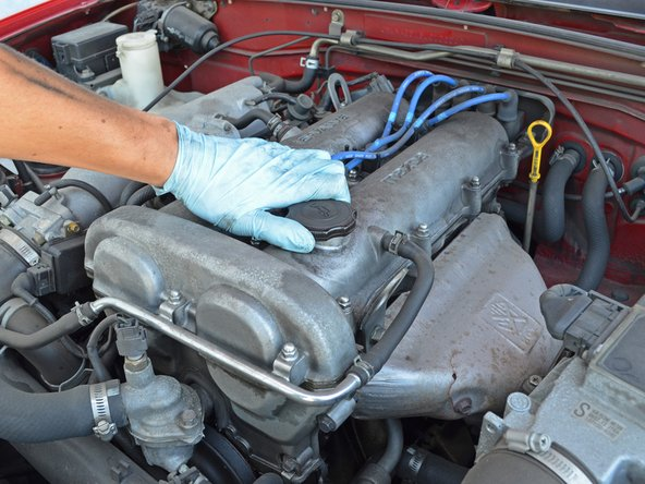 Remove the oil filler cap at the front of the engine by twisting it counter-clockwise and then lifting it up.