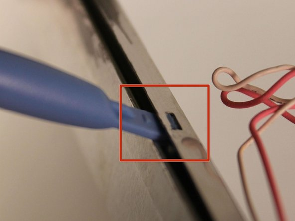 Using a plastic opening tool, unhook the latches on the side of the screen's metal enclosure.