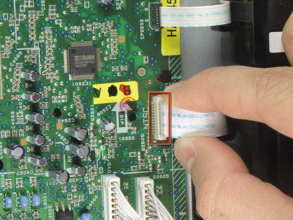 Remove the first of three ribbon cables on left hand side of disc drive by pulling vertically.
