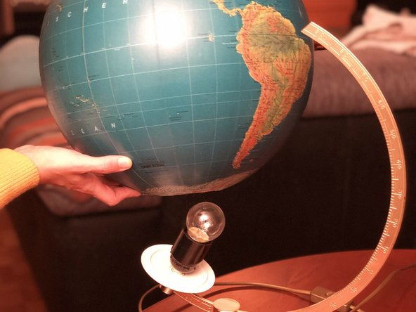 Now you can slowly turn the globe to the side and lift it from the socket at the south pole.