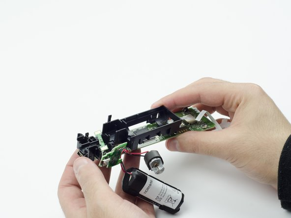 Carefully lift the entire circuit board from the black plastic encasing it.