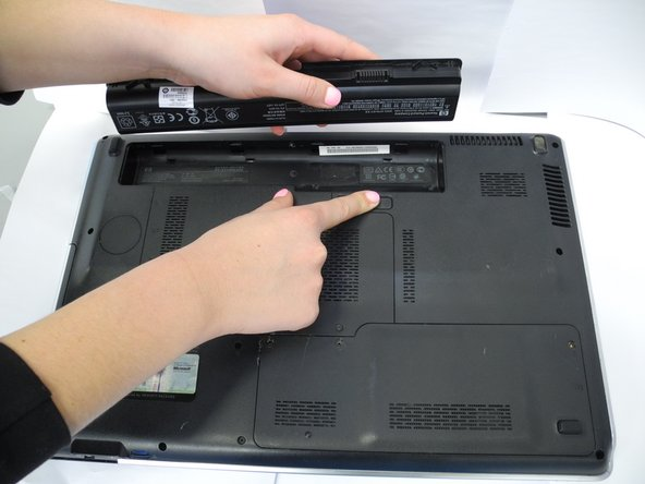 Carefully pull out the battery while holding the latch to the open position with your finger.
