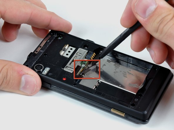 Insert the flat end of a spudger and pry downwards to release the plastic tab holding the rear case to the motherboard screw.