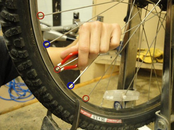 Loosen the spoke nipples that attach to the same side of the wheel that the caliper is touching. At the same time, tighten the spokes that attach to the opposite side of the hub.