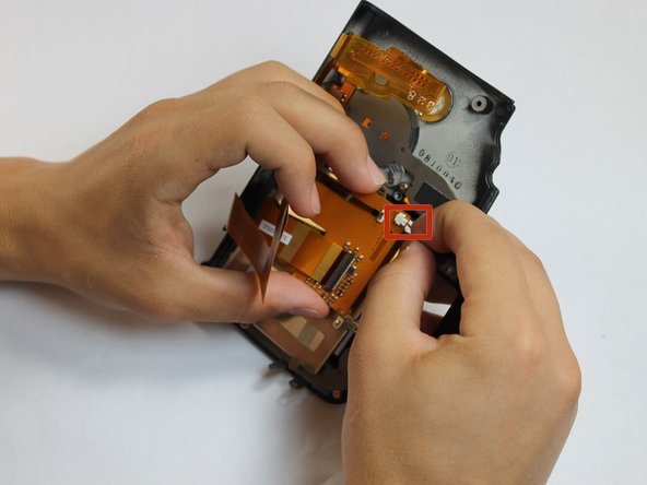 Grip the wire attaching the speaker to the data ribbon cable and pull it out.