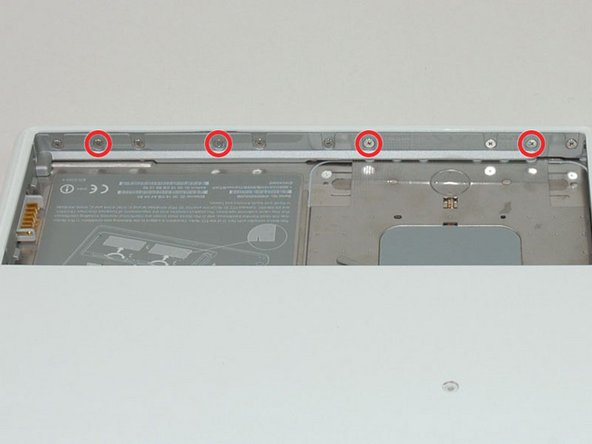 Remove the four 3 mm indicated Phillips #00 screws from the front wall of the battery compartment. When working from the left, remove the 2nd, 4th, 7th and 9th screw.