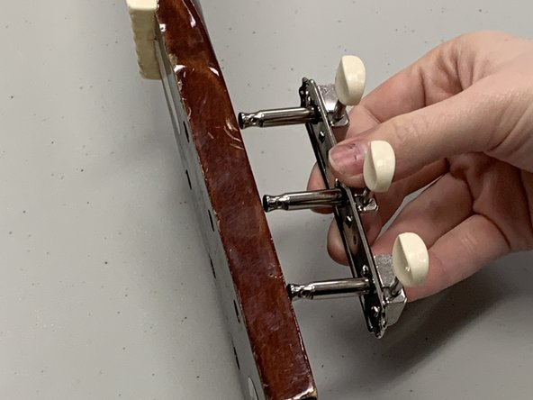 Insert one of the new tuning key racks into the appropriate tuning key holes.