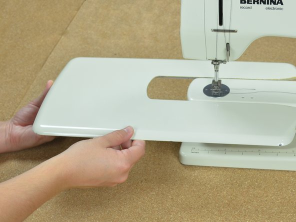 Slide the sewing machine table onto the machine.