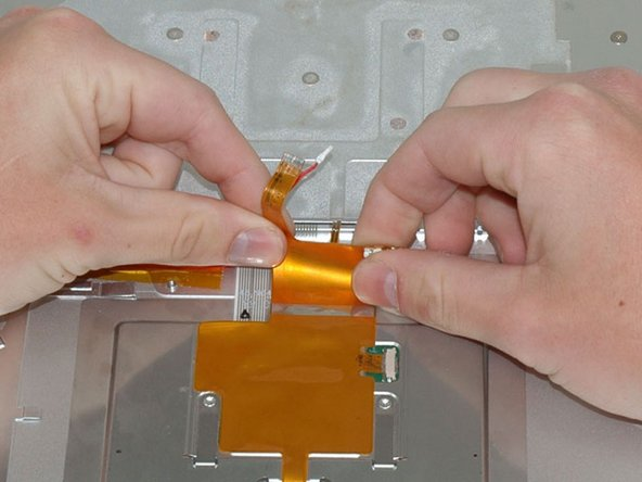Carefully grasp both sides of the large orange ribbon cable and gently peel the ribbon up from the upper case.