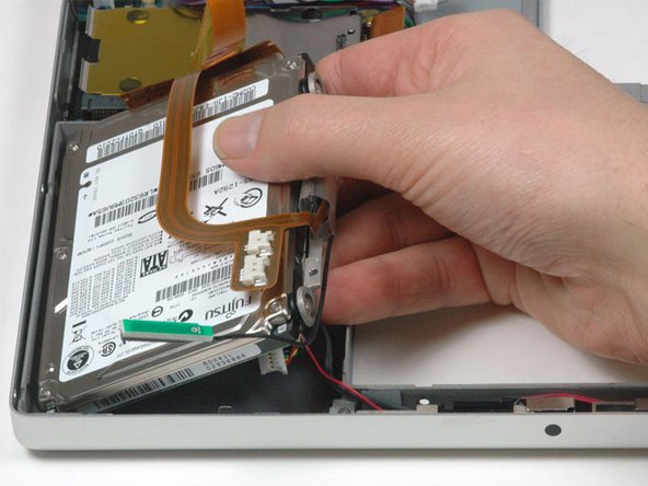 Lift the hard drive and retaining bracket up from the right side and remove it and the attached cable from the computer.