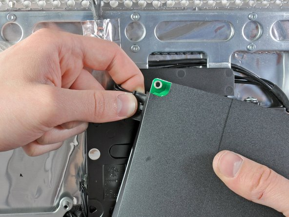 Rotate the power supply out of the rear case from its left side.
