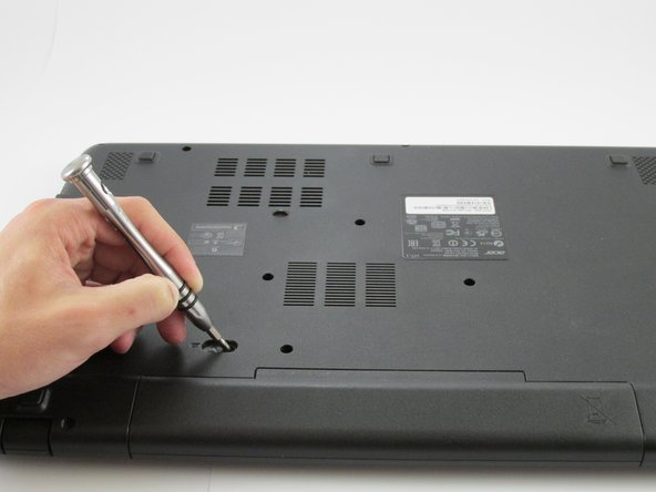 Use a small screwdriver or pen and place it into the battery lock as shown.