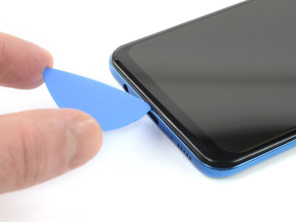 Insert an opening pick between the display and the midframe at the bottom of your phone above the USB-C port.