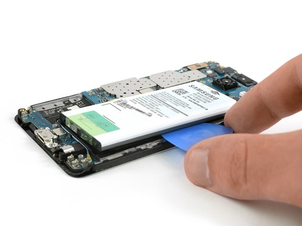 Insert an opening pick between the battery and the frame. Slide along the battery to separate the adhesive.