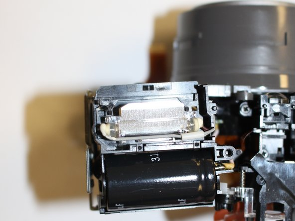 Use a spudger, or other thin object, to remove the capacitor from the housing. (Image 2)