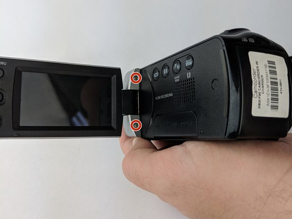 Rotate the camcorder so that back is facing you. Then flip open the LCD screen.