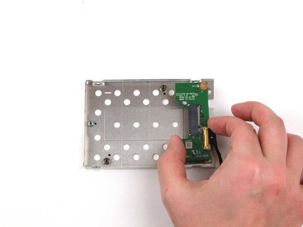Use your hand to remove the SSD connector board from the metal enclosure.
