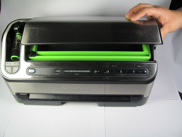 Open the device cover as shown in the image.