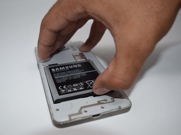 To remove the battery, lift up on the thumb tab located on the bottom right corner of battery bay.