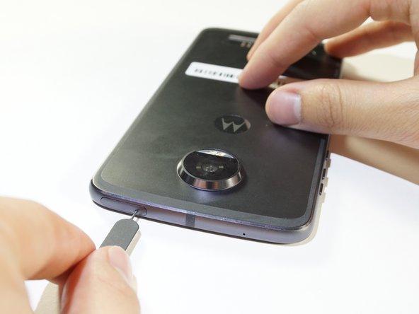 Rimuovi l'alloggiamento della scheda SIM premendo con decisione con l'attrezzo per la rimozione SIM nel foro nella parte superiore sinistra del telefono.