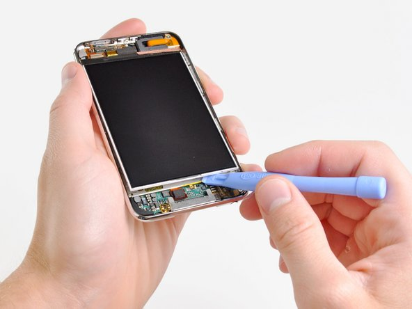 Insert a small iPod opening tool with the edge angled up toward the underside of the display between the white plastic backlight and the metal shield beneath it.