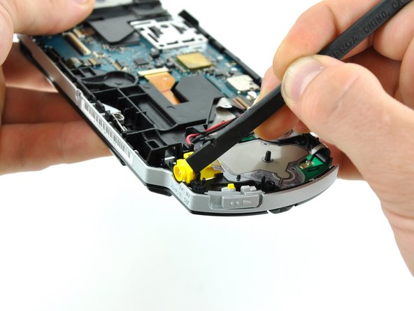 Using the flat edge of a spudger, pry the small black tab away from the power jack to free it from the case.
