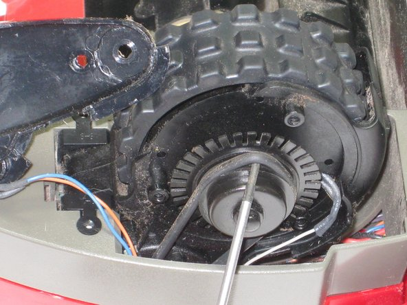 Using a screwdriver, gently remove the drive belt from the gear. This is the rubber band wrapped around the gear shaft.