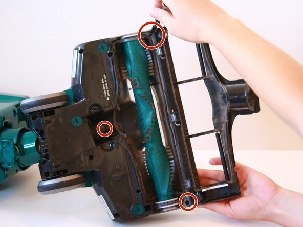 Using a T20 screwdriver, remove three 13.4 mm screws from where the roller brush cover attaches to the bottom of the vacuum.