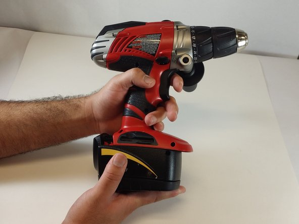 While holding down the red locking switch, slide the battery towards the back of the drill until the battery is fully removed from the drill.
