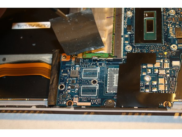 Remove the silver tape to reveal the fourth screw on the motherboard.