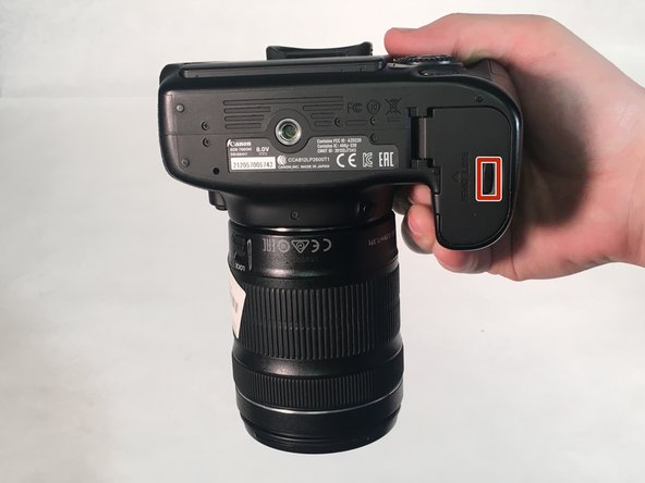 Hold the camera with the lens pointing down. Press the highlighted button with your finger to release the cover.