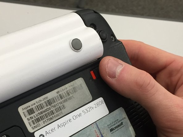Place your right thumb on the slide-release button under the battery on the right side.