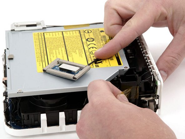 Remove the yellow tape securing the power button cable to the black plastic framework.