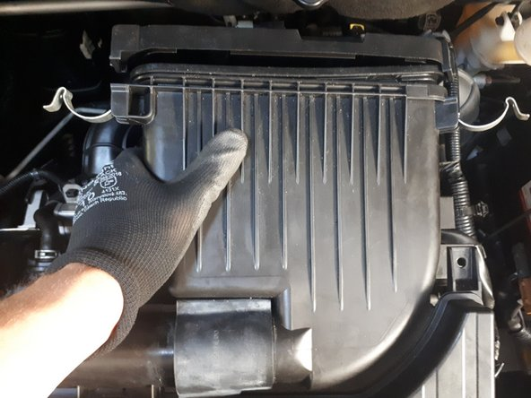 Grab the box at the left side and pull up and towards the right to pull the top part of air intake box out.